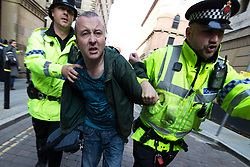 © Licensed to London News Pictures . 04/10/2015 . Manchester , UK .  Police detain a man as thousands of people at a demonstration against the Conservative government , organised by The People's Assembly , through Manchester City Centre , during the first day of the Conservative Party Conference in Manchester . Photo credit: Joel Goodman/LNP