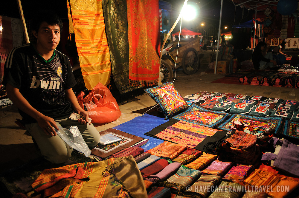 A vendor displays his woven textiles for sale at the night market on Quai Fa Ngum on the banks of the Mekong in Vientiane, Laos.