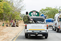 Armed police sitting on the backs of open vehicles during the police convoy , Save River Bridge, Inhambane Province, Mozambique