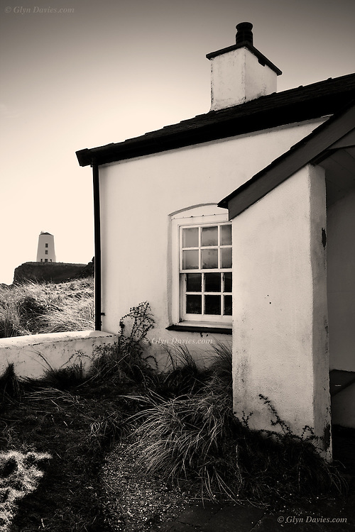 The old lighthouse, Twr Mawr can be seen beyond this end of four small cottages on Llanddwyn Island, Anglesey, which were built for the pilots who went out to meet boats needing to navigate into the ports further up the Menai Strait. This island was the home of Saint Dwynwen, the Welsh Patron Saint of Love. Llanddwyn Island is also an extension of the Newborough Nature Reserve.