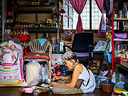 """21 JUNE 2017 - BANGKOK, THAILAND: A woman eats lunch in her shop in a community along the Chao Phraya River south of Krung Thon Bridge. This is one of the first parts of the riverbank that is scheduled to be redeveloped. The communities along the river don't know what's going to happen when the redevelopment starts. The Chao Phraya promenade is development project of parks, walkways and recreational areas on the Chao Phraya River between Pin Klao and Phra Nang Klao Bridges. The 14 kilometer long promenade will cost approximately 14 billion Baht (407 million US Dollars). The project involves the forced eviction of more than 200 communities of people who live along the river, a dozen riverfront  temples, several schools, and privately-owned piers on both sides of the Chao Phraya River. Construction is scheduled on the project is scheduled to start in early 2016. There has been very little public input on the planned redevelopment. The Thai government is also cracking down on homes built over the river, such homes are said to be in violation of the """"Navigation in Thai Waters Act."""" Owners face fines and the possibility that their homes will be torn down.          PHOTO BY JACK KURTZ"""