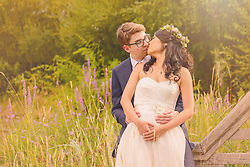 A romantic early evening photo of the bride and groom sharing a kiss in the beautiful grounds at the London Wetland Centre.