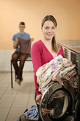 Young woman filling up cloths in washing machine while man in background