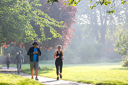 © Licensed to London News Pictures. 07/09/2021. London, UK. A runner and park users enjoy a warm misty morning in Chestnuts Park, north London as the mini heatwave continues in London. According to the Met office, temperatures over 28 degree Celsius are forecast today in London and the South East of England. Photo credit: Dinendra Haria/LNP
