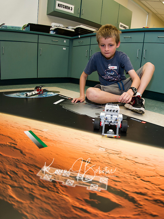 """Luke programs his Lego robotic droid for a mission on Mars during """"Let Go Your Mind"""" summer camp through Gilford Parks and Recreation held at the Gilford Middle School on Wednesday.  (Karen Bobotas/for the Laconia Daily Sun)"""