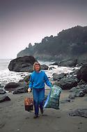 Environmental Volunteer woman carrying trash during coastal clean up day Muir Beach Marin County Coast California Women picking up trash off beach during Coastal Clean-up day, Muir Beach, Marin County coast, California