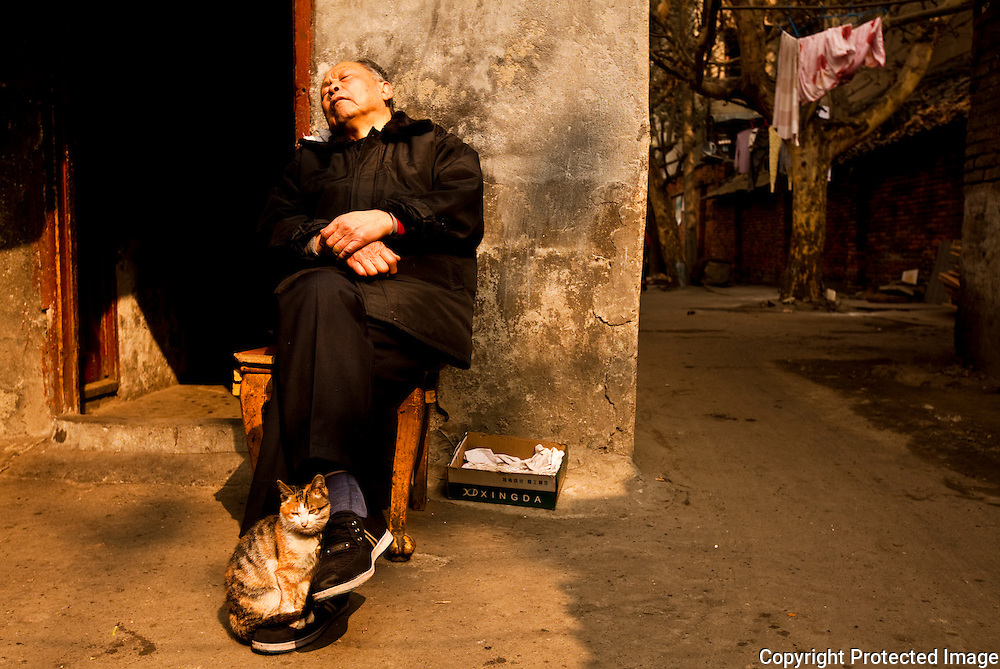 Man takes a nap with a cat in an alley in Chengdu