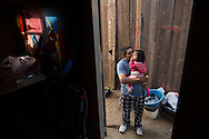 """Easton, CA<br /> Soledad Magana (23 years old)<br /> Hugo Magana (27 years old) <br /> Cesar Magana (2.5 years)<br /> Camila Magana (1 year old)<br /> This shot: Hugo plays outside the family trailor with daughter, Camila.<br /> <br /> Soledad and her mother stood hand in hand at the mobile pantry for the first time. <br /> <br /> Soledad's husband, Hugo, arrived in a small white car with their two children, Cesar and Camila, in the backseat.  As Soledad collected the distribution, Hugo worked to pack up the trunk.  The car made its way back to their home in Easton with the family of four—and a load of fresh bananas, carrots, bread, juices, lettuce, persimmons, and more. <br /> <br />  The family's home was a small trailer.  As Hugo unloaded the distribution Soledad held her baby girl in her arms and kept a careful ear out for little Cesar, who was busy making toys out of everything he could find.  Soledad smiled at the sight of the full kitchen.  """"Thank God,"""" she sighed, knowing that there would be food on the table that night. <br /> <br /> The young family had recently faced a series of hardships.  Due to the drought, Hugo was out of work.  The majority of his family and friends returned to Mexico, leaving them without a circle of support.  This caused them to move to Easton to be closer to Soledad's family.  Soledad also struggles to find work.  Without a GED and no English her options are limited.  However, she dreams of going back to school to be a dental hygienist.  To make ends meet in the short term, Hugo was hoping to find a job picking oranges or pruning that week.<br /> <br /> Family and extra support are what help this young couple survive.  $230 worth of food stamps monthly and the distribution from the community food bank both help them to make their rent payment of $370.  Once Cesar starts school, Soledad is grateful he'll be able to eat at the elementary cafeteria.  As food insecurity falls off their list of things to alleviate—for now—Hugo and Sole"""