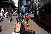 Waiting near a bus stop along Oxford Street in London, England, United Kingdom. This is the busiest shopping district in the capital with Oxford Street being the most crowded. Crowds can be so big that many people avoid the area altogether.