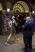 An eccentric man dressed in gold strides past theatre staff outside the Prince Edward Street in Londons Soho, on 19th October 2017, in London, England.