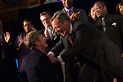 Nigel Farage, greets the business man and UKIP funder, Paul Sykes at a UKIP campaign meeting., The UK Indepenence Party, campaigns as an anti racist party whilst against immigration and the EU. The front rows of the hall are filled with multi ethnic supporters to reinforce the message.