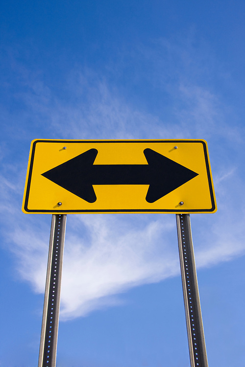 Confusing traffic direction sign pointing in opposing directions with blue sky background