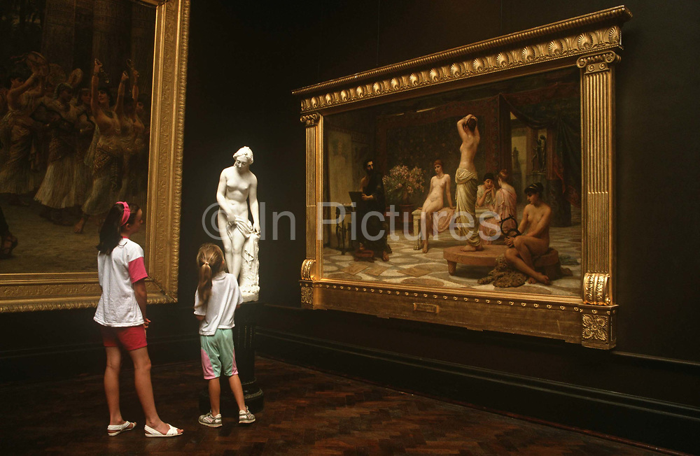 Two young girls admire a statuette in front of the painting called The Chosen Five (Zeuxis At Crotona) by Edwin Longsden Long. The youngsters stand looking at the figure finished off in a white marble-type of material who is seemingly looking down to speak with the girls. Two paintings of which one can be identified as Long's masterpiece occupy a corner of Gallery IV. Russell-Cotes Museum (formally, the Russell-Cotes Art Gallery & Museum) is an art gallery and museum in Bournemouth, England. It is located on the top of the East Cliff, next to the Royal Bath Hotel.