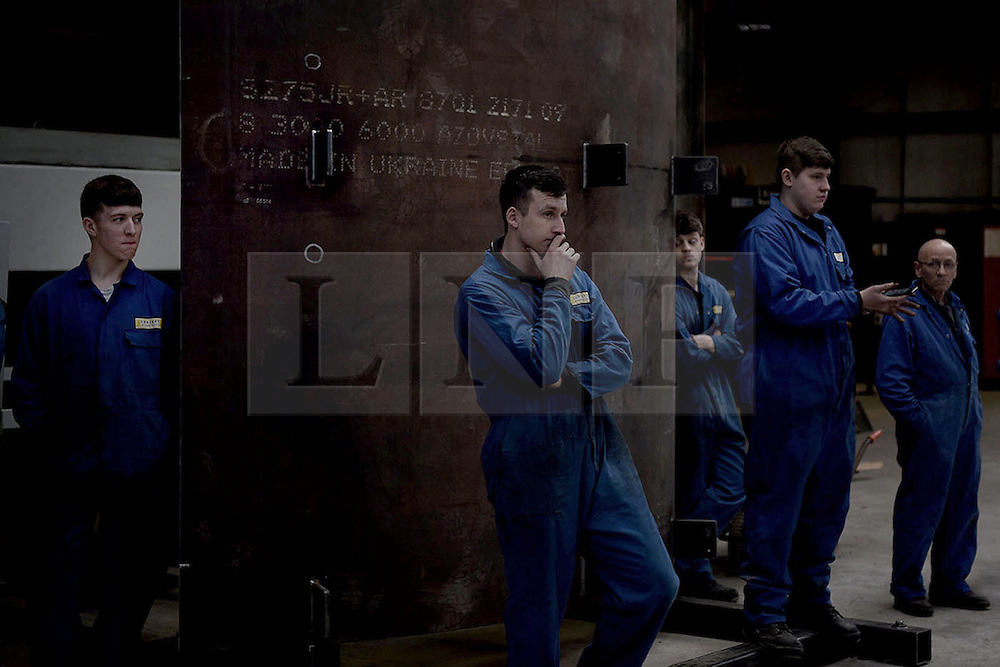 """© London News Pictures. """"Looking for Nigel"""". A body of work by photographer Mary Turner, studying UKIP leader Nigel Farage and his followers throughout the 2015 election campaign. PICTURE SHOWS - Metal workers at Concept Metals in Heywood & Middleton listen to Nigel Farage speaking about the country's economy, on March 23rd 2015. Mr Farage capitalised on the feelings of alienation that many working class and more 'blue collar' workers felt, trying to appeal to their sense of alienation during his election campaign. . Photo credit: Mary Turner/LNP **PLEASE CALL TO ARRANGE FEE** **More images available on request**"""