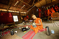 A monk in a shared room surrounded by the traditional red and orange robes, cleans his alms bowl after the only daily meal.
