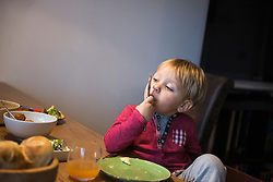 Little boy licking his finger at breakfast table, Munich, Germany