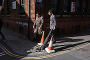 Two male pedestrians walk past a broken post that leans over after being pushed over by a unknown vehicle.