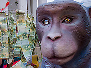 16 NOVEMBER 2013 - BANGKOK, THAILAND: A monket statue looks over money donated to Wat Saket at the Wat Saket Temple Fair in Bangkok. Wat Saket is on a man-made hill in the historic section of Bangkok. The temple has golden spire that is 260 feet high which was the highest point in Bangkok for more than 100 years. The temple construction began in the 1800s in the reign of King Rama III and was completed in the reign of King Rama IV. The annual temple fair is held on the 12th lunar month, for nine days around the November full moon. During the fair a red cloth (reminiscent of a monk's robe) is placed around the Golden Mount while the temple grounds hosts Thai traditional theatre, food stalls and traditional shows.     PHOTO BY JACK KURTZ
