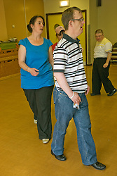 Day Service users with learning disability taking part in line dancing class with a Care Assistant joining in the activity,