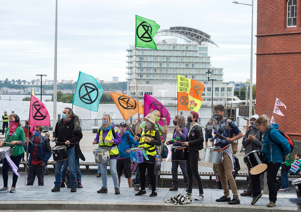 """© Licensed to London News Pictures;02/09/2020; Cardiff, Wales, UK. Extinction Rebellion protest in Cardiff Bay in front of the Senedd, the Welsh Government building, in support of the upcoming Climate and Ecological Emergency Bill. Today the protest is """"Rising Tide Action!!"""" focusing on the impact that the climate crisis is having locally and across Wales because it is impacting weather cycles, flooding, air pollution and our food security. The protest involved arts, theatre, speakers, music, banners and a drown in. The protest is part of a national protest over the next two weeks including London and other cities in the UK against climate change. XR say that despite clear scientific evidence of the deadly climate and ecological emergency, the UK government are refusing to take the urgent action needed to avoid mass extinction, and that politicians need to support the Climate and Ecological Emergency Bill. During the coronavirus covid-19 pandemic, climate change is being forgotten but it is still an emergency that is happening. The protest was socially distanced and participants wore masks. Photo credit: Simon Chapman/LNP."""