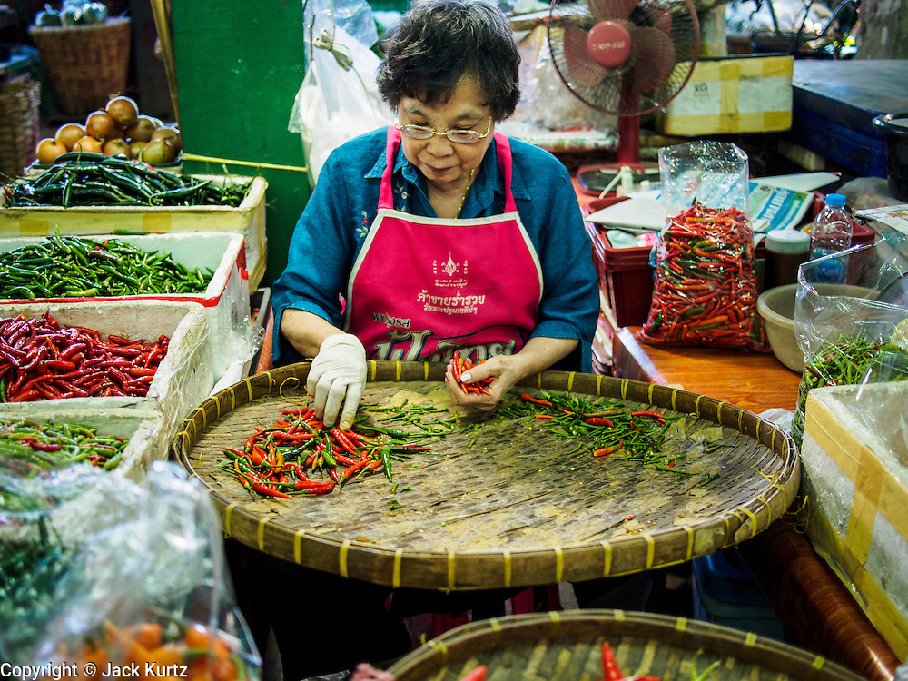 """19 DECEMBER 2013 - BANGKOK, THAILAND:    A woman sorts chilies for sale in the flower market. Pak Khlong Talat (""""the market at the mouth of the canal"""") is a market in Bangkok that sells flowers, fruits, and vegetables. It is the primary flower market in Bangkok. It is located on Chak Phet Road and adjacent side-streets, close to Memorial Bridge. The market is open 24 hours, but is busiest before dawn, when boats and trucks arrive with flowers from nearby provinces.       PHOTO BY JACK KURTZ"""