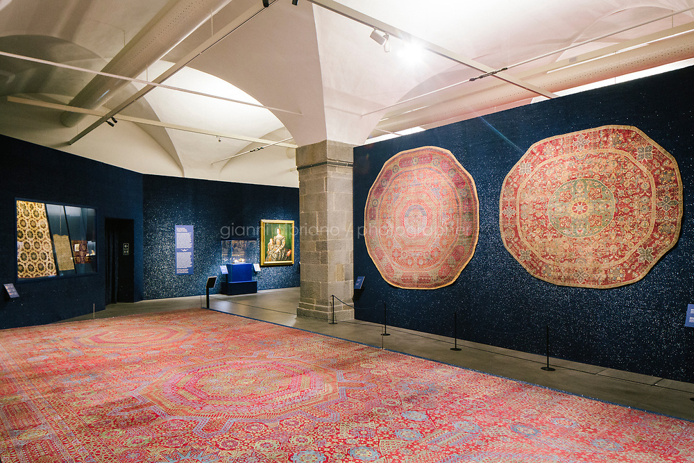 """FLORENCE, ITALY - 28 JULY 2018: Carpets manufactured in Cairo (Egypt) in the 16th century are seen here at the exhibition """"Islamic Art and Florence from the Medici to the 20th century"""" at the Uffizi Gallery in Florence, Italy, on July 28th 2018.<br /> <br /> """"Islamic Art and Florence from the Medici to the 20th century"""", curated by Giovanni Curatola and organised by the Uffizi  offers visitors the opportunity to discover the knowledge, exchange, dialogue and mutual influence that existed between the arts of East and West. The exhibition illustrates the extremely important role that Florence played in interfaith and intercultural exchange between the 15th and the early 20th centuries.<br /> <br /> According to Eike Schmidt, the Director of the Gallerie degli Uffizi, """"the exhibition not only highlights the interest in Islamic culture that was strongly rooted in Medici collectintg and that continued well into the modern era, but it also testifies to the unprejudiced aesthetic fascination with the Orient that has always permeated European art. At the same time, it draws our attention to the crucial importance of trade, but primarily of intellectual and human exchange, in the Mediterranean basin and beyond as a means of enrichment and of peace""""."""