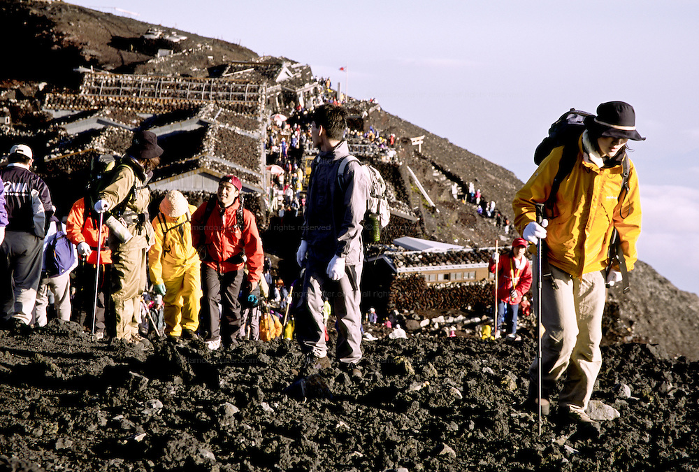 Climbers start to traverse the crater rim of Mount Fuji, at 3,776 metres, the highest peak in Japan. Yamanashi Prefecture, Japan August 2005
