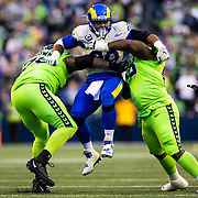Los Angeles Rams defensive end Aaron Donald (99) is blocked by Seattle Seahawks offensive tackle Duane Brown (76) and Seattle Seahawks offensive guard Damien Lewis (68) during an NFL regular season football game on Thursday, Oct. 7, 2021 in Seattle. The Rams won, 26-17. (Ric Tapia via AP)