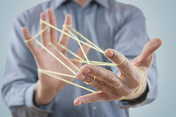 Mid section view of a man's hands making a cats cradle with string, Bavaria, Germany