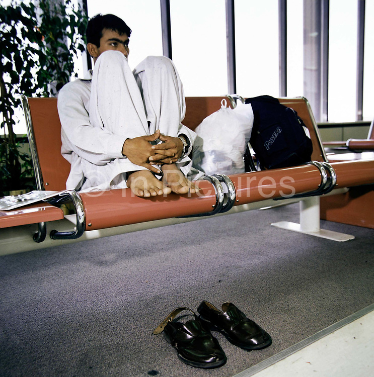 With feet up on airport seating, a migrant worker awaits his homeward flight from Bahrain to South-Asia. Sitting with legs gathered and with shoes removed - in the manner that people subjected to fierce desert or tropical heat try to keep cool, although in this airpirt terminal building, air-conditioning allows more comfort. The young man works on building projects somewhere in the middle-east region and is either in transit of beginning his jounrey to India, Pakistan or perhaps Bangladesh, seen here months before the terrorist attacks on America that changed the public's attitude to flying on commercial airliners.