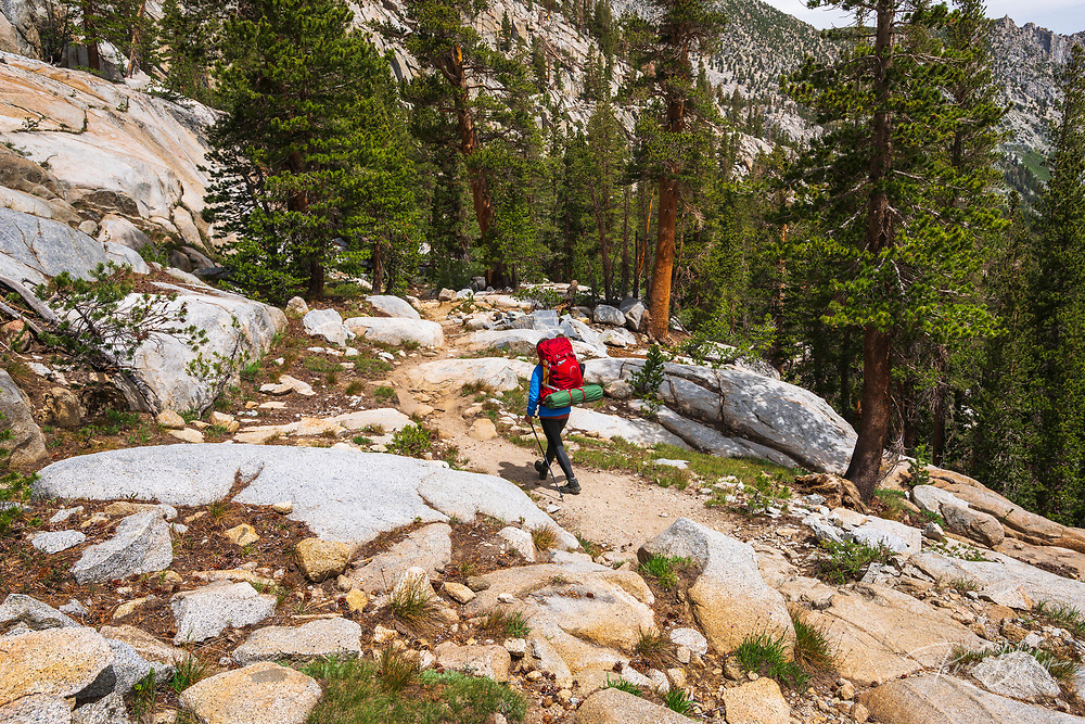 Backpacker on the Treasure Lakes trail, John Muir Wilderness, Sierra Nevada Mountains, California USA