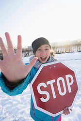 Portrait of girl holding stop sign