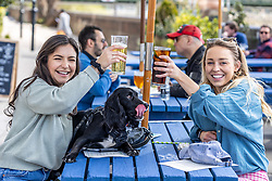 Licensed to London News Pictures. 12/04/2021. London, UK. Thirsty work. Pub goers (left) Gabriella Lucena 24 and Gabrielle West 28 with 1 year old Lola a Cocker Spaniel enjoy a pint and a soft drink along the Thames at Hammersmith, West London for the fist time in months as pubs and shops across England welcome back customers after Covid-19 restrictions were lifted today. Prime Minister Boris Johnson announced last week that non-essential shop, restaurants with outside seating , hairdressers and gyms can reopen today after 4 months of Covid-19 lockdowns. Photo credit: Alex Lentati/LNP