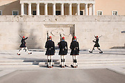 Exterior of the Old Royal Palace, the building that houses the Hellenic Parliament with two Greek men, Evzones and members of the Proedriki Froura or the Presidential Guard, guarding the Tomb of the Unknown Soldier in the foreground, Athens, Greece
