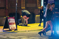 """© Licensed to London News Pictures . 15/12/2017. Manchester, UK. A man changes his trousers on a street off Deansgate . Revellers out in Manchester City Centre overnight during """" Mad Friday """" , named for historically being one of the busiest nights of the year for the emergency services in the UK . Photo credit: Joel Goodman/LNP"""
