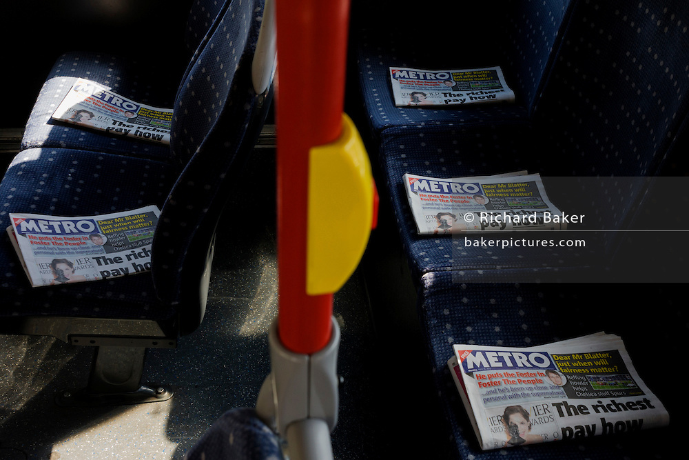 Copies of the free daily tabloid Metro newspaper carefully placed on upper deck of seats on a London bus.