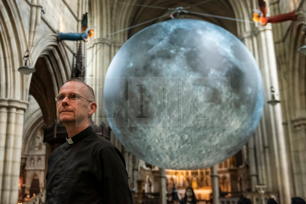 © Licensed to London News Pictures. 19/08/2021. LONDON, UK.  Vicar James Heard poses in front of Luke Jerram 's Museum of the Moon, a 7m diameter artwork featuring detailed NASA imagery of the lunar surface.  At an approximate 1:500,000 scale, each centimetre of the internally lit sphere represents 5km of the moon's surface. The touring artwork is on display until 30 August at St John the Baptist Church near Shepherd's Bush and forms part of this year's Kensington and Chelsea Festival.  Photo credit: Stephen Chung/LNP