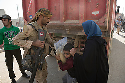 Licensed to London News Pictures. 11/11/2016. Mosul, Iraq. A soldier, of the Iraqi Army's 9th Armoured Division, hands a sack of food to a female resident of Mosul's Al Intisar district during a visit by his unit. The Al Intisar district was taken four days ago by Iraqi Security Forces (ISF) and, despite its proximity to ongoing fighting between ISF and ISIS militants, many residents still live in the settlement without regular power and water and with dwindling food supplies.<br /> <br /> The battle to retake Mosul, which fell June 2014, started on the 16th of October 2016 with Iraqi Security Forces eventually reaching the city on the 1st of November. Since then elements of the Iraq Army and Police have succeeded in pushing into the city and retaking several neighbourhoods allowing civilians living there to be evacuated - though many more remain trapped within Mosul.  Photo credit: Matt Cetti-Roberts/LNP