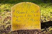 Old lichen covered gravestone in graveyard  village parish church of All Saints, Yatesbury, Wiltshire, England, UK