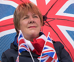 Trafalgar Square, London, June 12th 2016. Rain greets Londoners and visitors to the capital's Trafalgar Square as the Mayor hosts a Patron's Lunch in celebration of The Queen's 90th birthday. PICTURED: A woman's scarf, flags and umbrella typify the patriotic nature of the day.