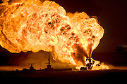 One of the oil wells set ablaze by retreating Iraqi troops in the southern Iraq Rumaila oil field. The wells were set on fire with explosives placed by retreating Iraqi troops when the US and UK invasion began. Seven or eight wells were set ablaze but at least one other was detonated but did not ignite. The Rumaila field is one of Iraq's biggest with five billion barrels in reserve. Many of the wells are 10,000 feet deep and produce huge volumes of oil and gas under tremendous pressure, which makes capping them very difficult and dangerous. Rumaila is also spelled Rumeilah.