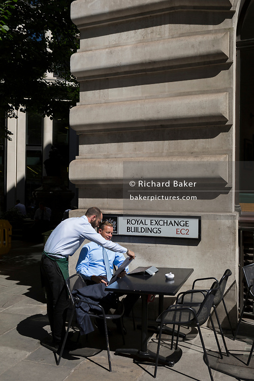 A waiter helps with the menu in hot sunshine outside a restaurant in Royal Exchange Buildings during the 2018 heatwave in the City of London, the capital's historic financial district, on 2nd August 2018, in London, England.