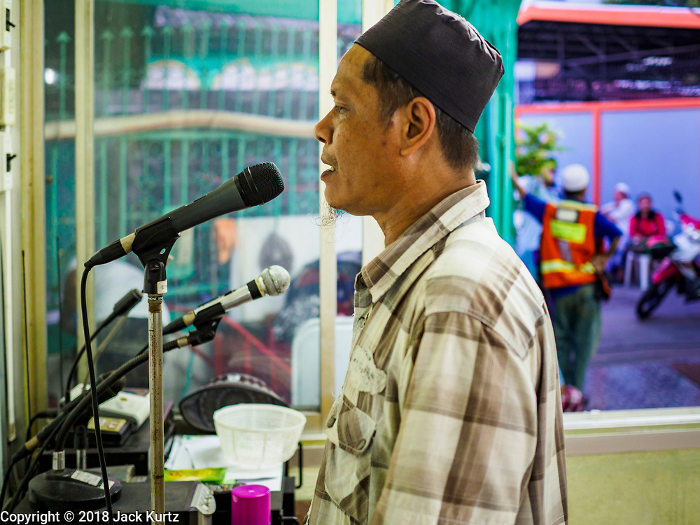 16 MAY 2018 - BANGKOK, THAILAND: The muezzin at Masjid (Mosque) Darul Falah, a small mosque in Baankrua, the oldest Muslim neighborhood in Bangkok recites the Call to Prayer before evening prayers on the first night of Ramadan. Based on the sighting of the new moon, Ramadan fasting starts on Thursday, 17 May in Thailand.      PHOTO BY JACK KURTZ