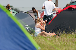 © Licensed to London News Pictures. 18/07/2014. Southwold, UK.   A girl puts her makeup on on a hot sunny morning next to her tent  Latitude Festival 2014 Day 1. Today is expected to be the hottest day of the year with temperatures forecast to reach 32 degrees centigrade.   Latitude is an British annual music festival.  Photo credit : Richard Isaac/LNP