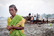 60 yr old Janaki survived the tsunami, but 12 of her family didn't. Her husband, her two sons, her two daughters in law and her five grandchildren were all killed last sunday. For the last six days she has been in a relief camp to terrified of the sea to return to her home in Akkaraipet, the area that housed fishermen in Nagapattinum. Such was the extreme devestation to the area she couldn't find the remains of her home and was walking around in a severe state of shock looking for members of her family. In the background the body collectors as they are known search for bodies in the remains of a wrecked home. They were to find the bodies of pregnant woman, her husband and two small children.