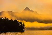 Peaks sticking out of fog banks at sunrise along the Inside Passage, near Sitka, Alaska USA.