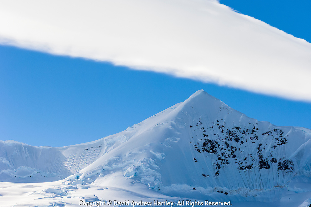 Cloud formation above a pristine snow covered mountain, Neko Harbor, Andvord Bay, Antarctica