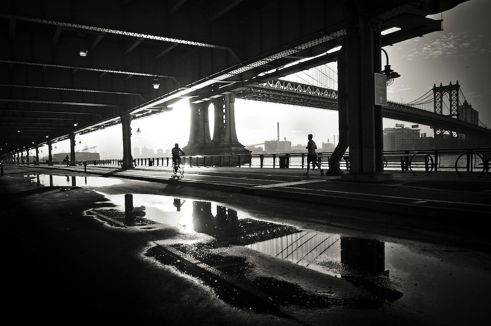 Reflections in a puddle on the East River Bikeway in Lower Manhattan, by the Manhattan Bridge, at sunrise, New York.