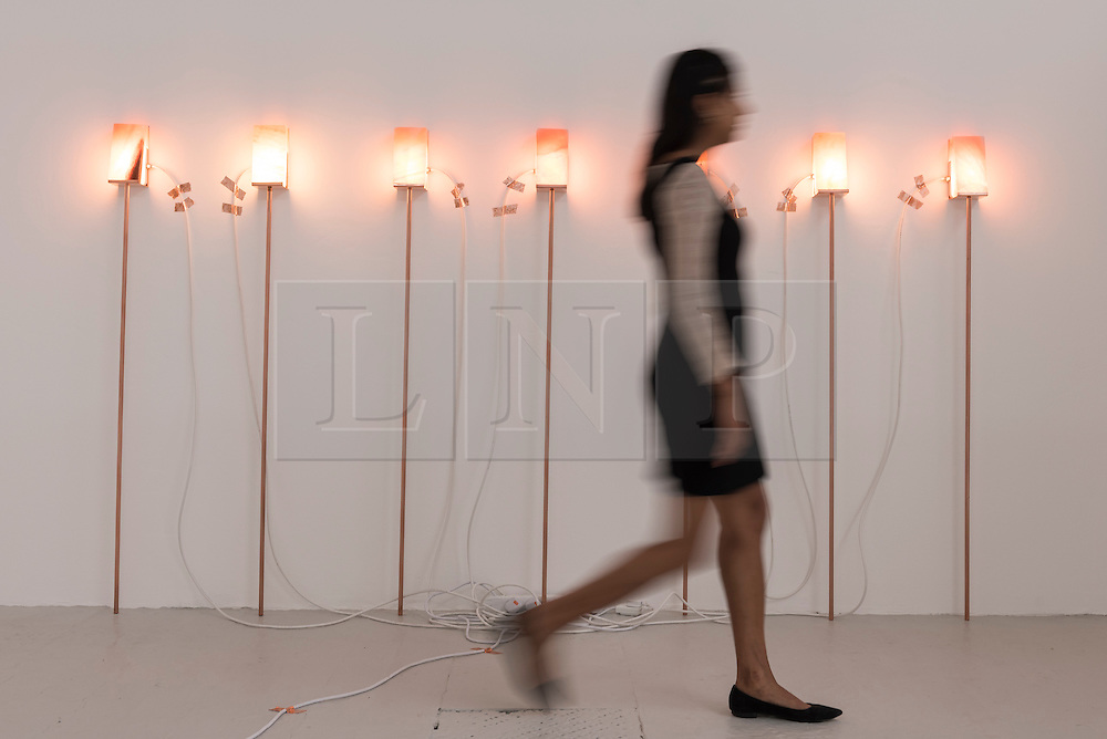 """© Licensed to London News Pictures. 22/06/2016. London, UK. A staff member walks by the """"Capsule"""" light installation by Wanda Wieser at the annual exhibition of works by artists graduating from the UK's longest established art school, RA Schools Show, at the Royal Academy in Piccadilly.  Works from 17 emerging artists are on show 23 June to 3 July. Photo credit : Stephen Chung/LNP"""