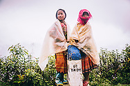Two ethnic kids stand on a kilometer marker in Ha Giang Province, Vietnam, Southeast Asia